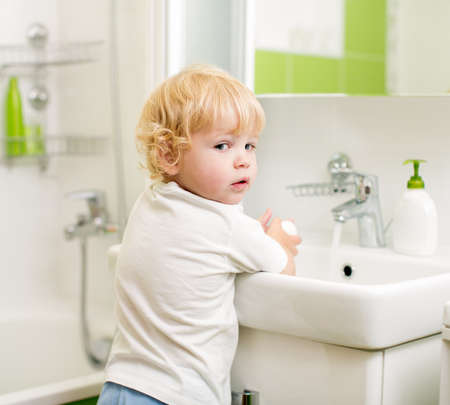 kid washing hands with soap in bathroom photo