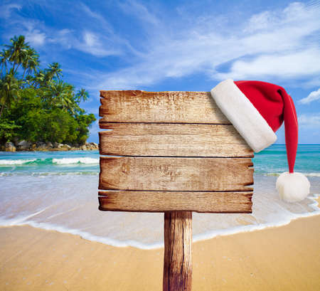 a signboard: Christmas on beach  Wooden signboard with Santa Stock Photo