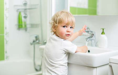 kid washing hands in bathroom photo