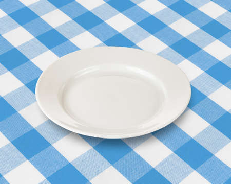 plate or dish over blue checked fabric tablecloth photo