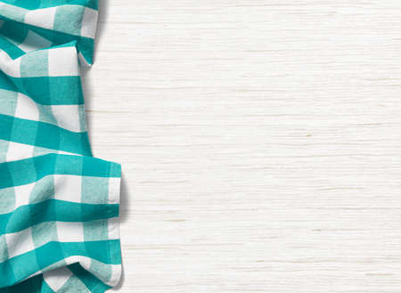 checker plate: folded cyan tablecloth on bleached wooden table Stock Photo