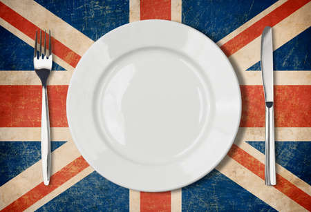 Plate, fork and knife on grunge UK flag photo
