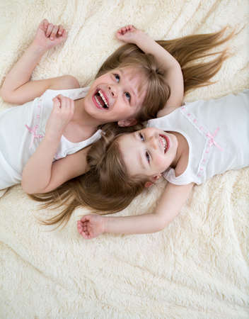 happy little girls lying on bed photo