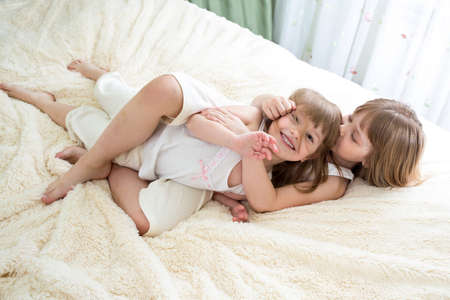 happy little girls sisters hugging and kissing on bed photo