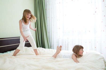 Two sisters playing on bed together photo
