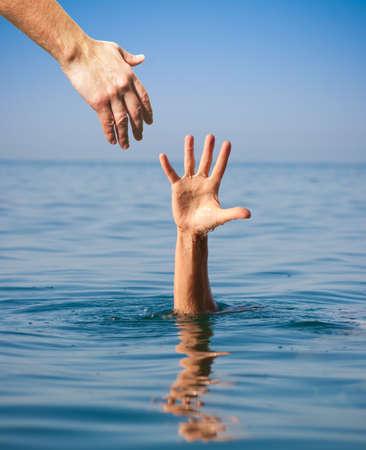 dando la mano: ayudar a la mano que da al hombre que se ahoga en el mar Foto de archivo