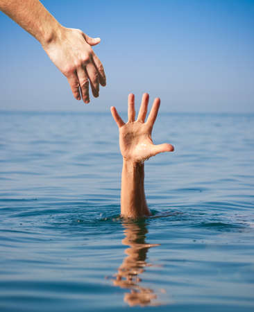 helping hand giving to drowning man in sea photo