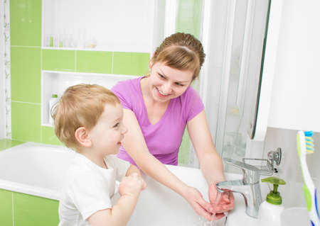 Happy mother and kid washing hands with soap together in bathroom photo