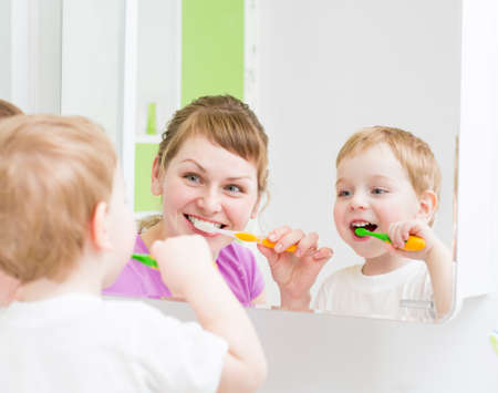 Happy mother and child teeth brushing  in bathroom front of mirror photo