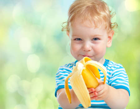 curly headed: happy kid eating banana fruit  healthy food eating concept