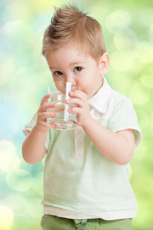 Boy drinking water from glass photo