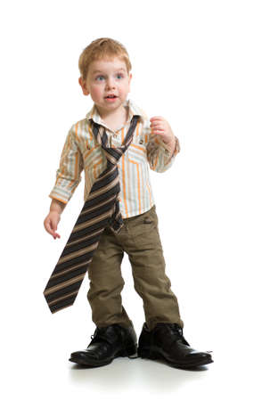 adultos: muchacho que juega con los zapatos grandes del padre aislados