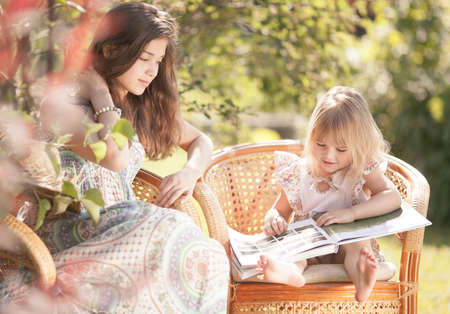Girls reading book outdoor in summer day  Retro stylized  photo