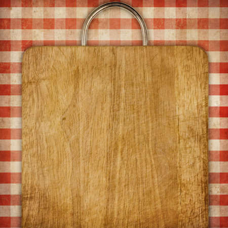hardboard or breadboard over red checked gingham picnic tablecloth grunge background Stock Photo