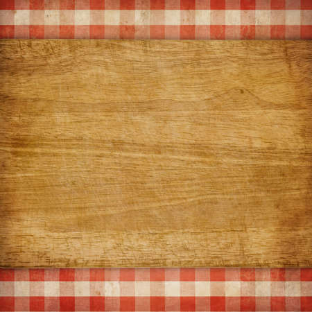 Cutting board over red grunge checked gingham picnic tablecloth background photo