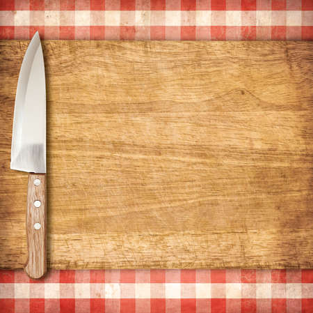 red tablecloth: Cutting breadboard and knife over red grunge gingham tablecloth background