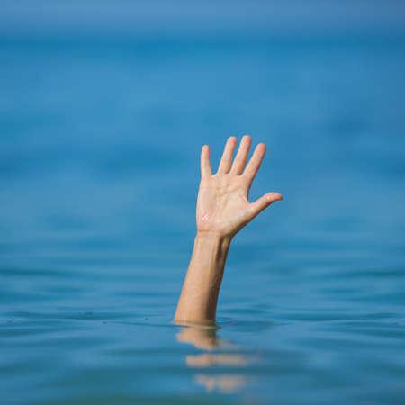 ahogarse: mano del hombre que se ahoga en el mar para pedir ayuda