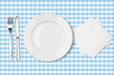 plate, fork, knife and napkin over blue checked fabric tablecloth top view photo