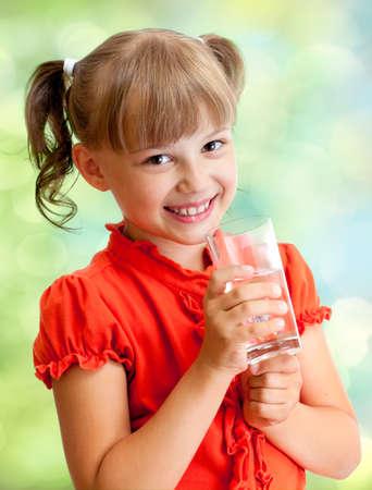 girl drinking water: Schoolgirl portrait with water glass outdoor