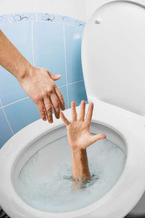 savings problems: Mans hand in toilet bowl or WC flushing and another hand helping Stock Photo