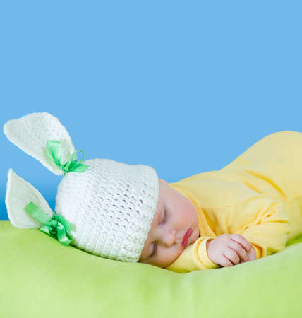 sleeping baby closeup portrait in hare or rabbit hat with expandable blue copyspace photo