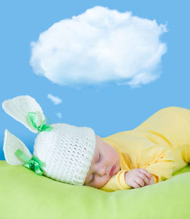 sleeping baby closeup portrait in hare or rabbit hat with dream cloud photo