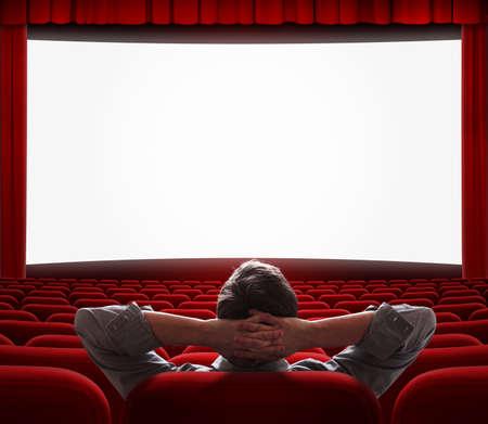 home theater: un uomo rilassato, seduto da solo con il comfort come a casa davanti al grande schermo nel vuoto sala cinema