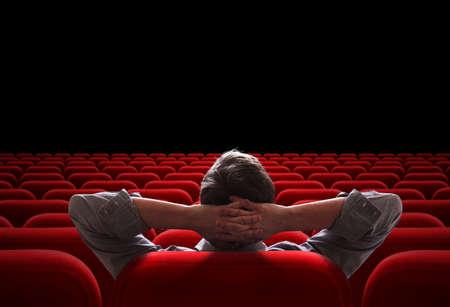 空の映画館や劇場の講堂で座っている一人の男