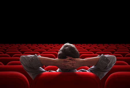 auditorium: one man sitting in empty cinema or theater auditorium