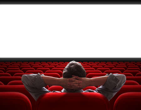 man sitting alone in empty cinema hall photo