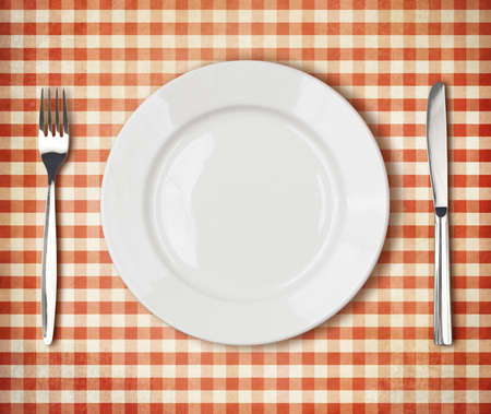 checker plate: white plate, fork, knife top view over old red picnic tablecloth