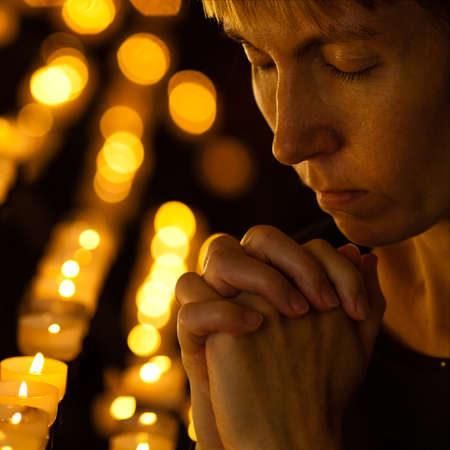 Prayer praying in Catholic church near candles. Religion concept. photo