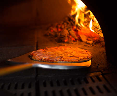 fire bricks: Ready pizza getting from oven