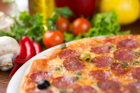 salami sausages pizza closeup on table with vegetables photo