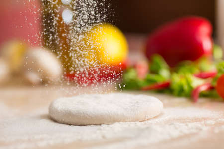 Dough for Italian pizza preparation. Falling flour. Stock Photo