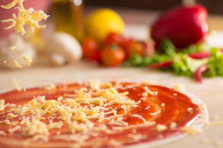 Italian pizza preparation with cheese falling. photo