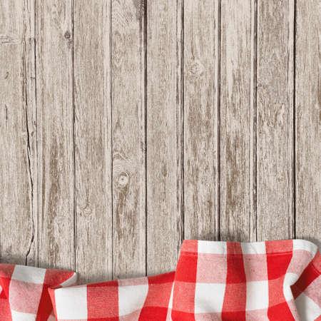 trompo de madera: vieja mesa de madera con fondo rojo mantel de picnic Foto de archivo