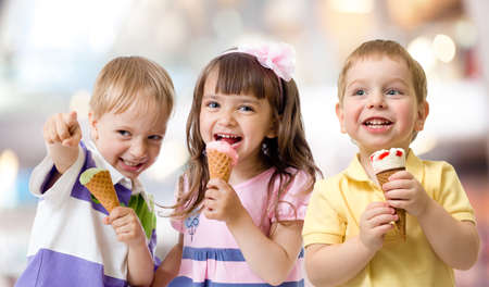 comiendo: grupo de ni�os divertidos bromeando con helado en la parte