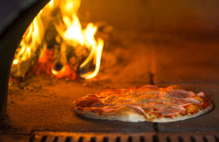 making a fire: Pizza baking in traditional oven