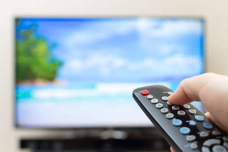 Program switching or button pressing on TV remote control photo