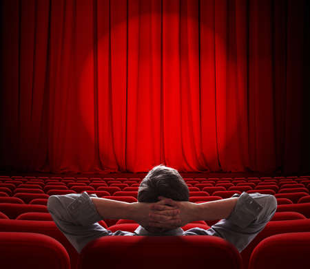 funny movies: man sitting alone in  empty theater or cinema hall Stock Photo