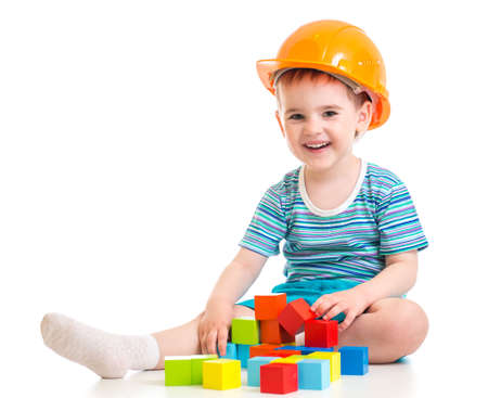 kid boy in hard hat with colorful building blocks photo