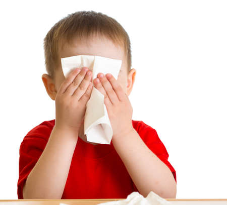 Child nose wiping with tissue photo