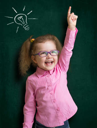 Happy kid girl in glasses with bright idea standing near school blackboard in classroom photo