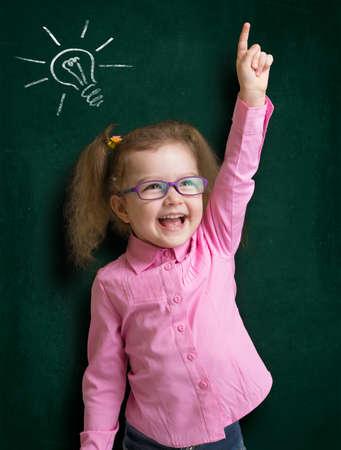 Prodigy: Szczęśliwy dzieciak dziewczyna w okularach z jasnym pomysł stojący w pobliżu szkoły tablica w klasie Zdjęcie Seryjne