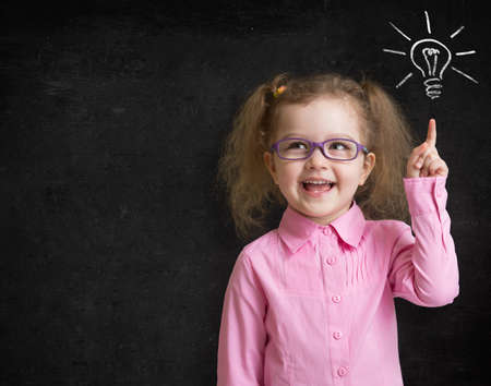 Happy kid girl in glasses with bright idea standing near school blackboard in classroom