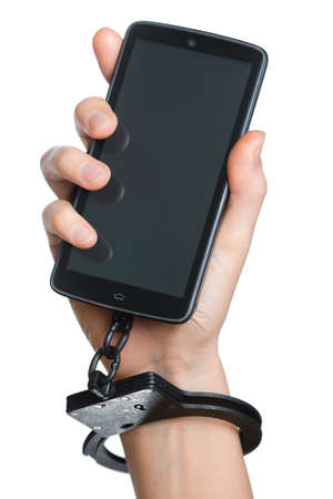 unfreedom: Mobile phone addiction concept. Smartphone and handcuff in hand isolated on white. Stock Photo