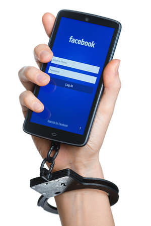 crime: TOMSK, RUSSIA - MAY 22, 2014: Hand chained with smartphone where facebook application started. According to wikipedia.org Facebook has over one billion active users. Some users become addicted to the social networking sites such as Facebook.