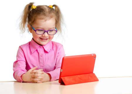 computer case: smiling kid in glasses looking at mini tablet pc screen sitting at table Stock Photo