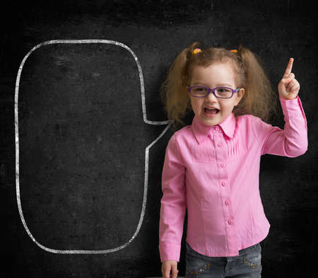 Funny child in eyeglasses standing near school chalkboard  as a teacher with blank speech bubble scetch